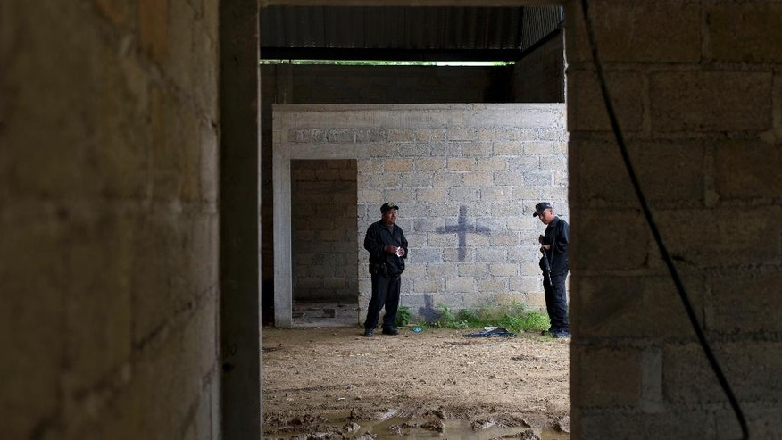 FILE - In this July 3, 2014, file photo, state police stand inside a warehouse where a black cross covers a wall near blood stains on the ground, after a shootout between Mexican soldiers and alleged criminals on the outskirts of the village of San Pedro Limon, in Mexico state, Mexico. Leading Mexican human rights groups announced Wednesday, March 30, 2016, that a military court acquitted six of seven soldiers charged with breach of discipline in the 2014 killings. (AP Photo/Rebecca Blackwell, File)