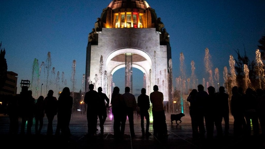 FILE - In this Dec. 26, 2012 file photo, pedestrians stand in front of the Arch of the Revolution monument in Mexico City. Moody's credit rating agency has changed the outlook for Mexico's debt rating from stable to negative, citing low oil prices and slow economic growth, according to a Moody's statement on Thursday, March 31, 2016. (AP Photo/Alexandre Meneghini, File)