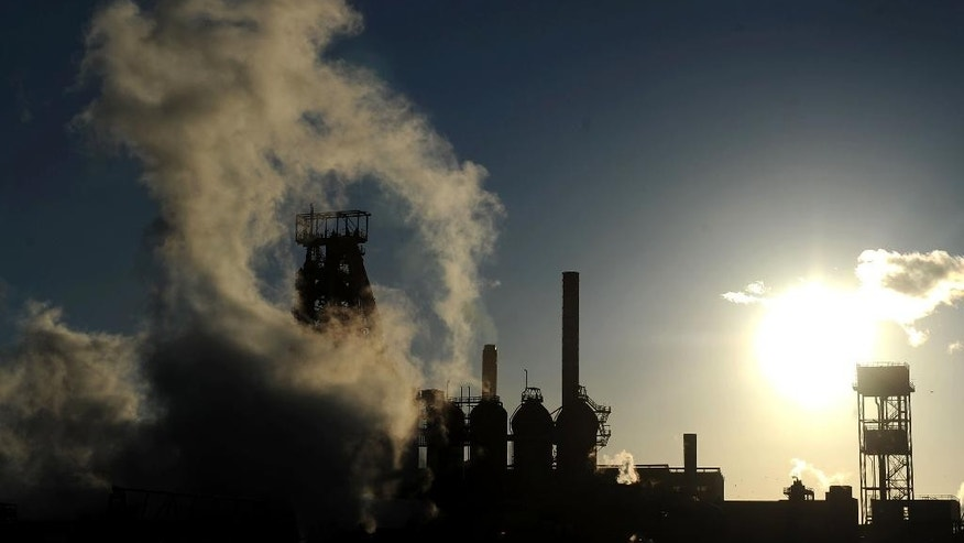 The sun sets as smoke and steam rises from the Tata steel plant in Port Talbot, Wales, Wednesday March 30, 2016, after the steel giant confirmed plans to sell its UK assets. After a meeting at the company's headquarters in Mumbai, India, Tata Steel said Wednesday it is seeking a buyer for its UK steel making plants, an announcement which shocked steel workers, industry unions, and the British government who have appealed for time to save the country's biggest steel maker. (Andrew Matthews  / PA via AP) UNITED KINGDOM OUT - NO SALES - NO ARCHIVES