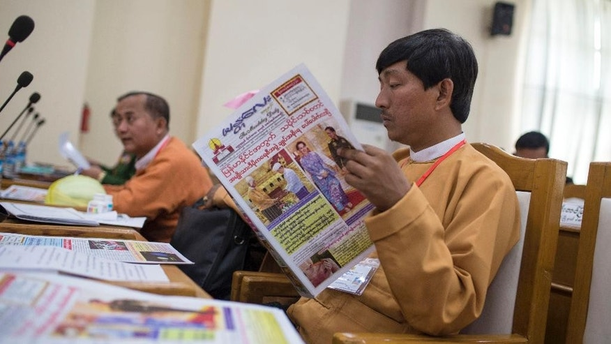 "A member of Mandalay regional parliament reads ""Mandalay Daily"" newspaper featuring Myanmar's key lawmakers and power transition in Mandalay, Myanmar, Thursday, March 31, 2016. Aung San Suu Kyi's aide Htin Kyaw took oath on Wednesday as a new civilian government took over Myanmar, after 54 years of rule by the junta or its proxy. (AP Photo/Hkun Lat)"