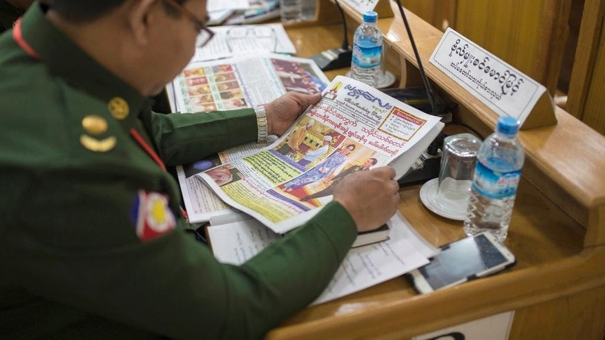 An appointed military officer and a member of the Mandalay regional parliament reads a copy of the Mandalay Daily newspaper featuring Myanmar's key lawmakers and power transition in Mandalay, Myanmar, Thursday, March 31, 2016. Aung San Suu Kyi's aide Htin Kyaw took oath on Wednesday as a new civilian government took over Myanmar, after 54 years of rule by the junta or its proxy. (AP Photo/Hkun Lat)