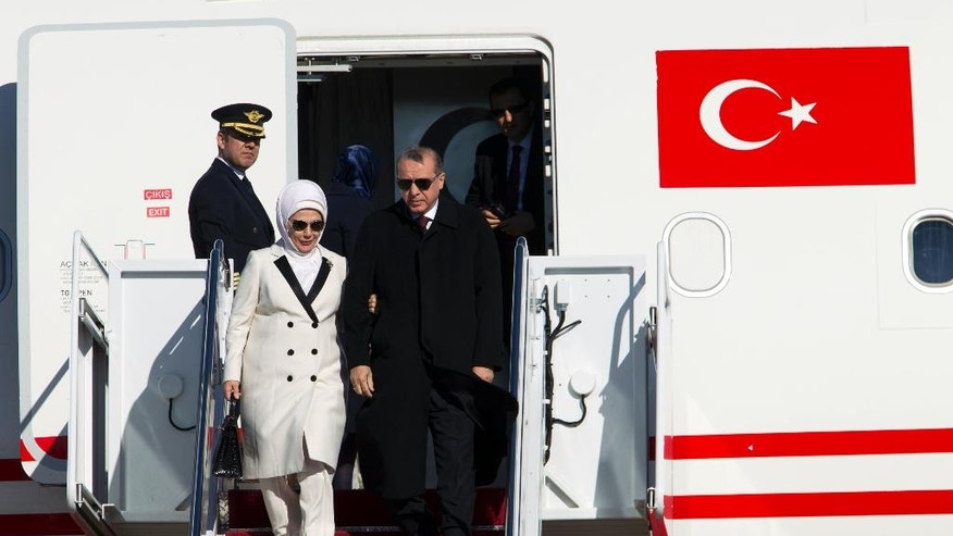 Turkish President Recep Tayyip Erdogan accompanied by his wife Emine walk down the stairs upon his arrival at Andrews Air Force Base, Md., Tuesday, March 29, 2016. Erdogan is in Washington to attend the Nuclear Security Summit. (AP Photo/Jose Luis Magana)