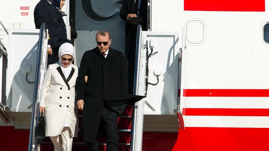 Turkish President Recep Tayyip Erdogan, accompanied by his wife Emine walk downstairs from a plane upon his arrival at Andrews Air Force Base, Md., Tuesday, March 29, 2016. Erdogan is in Washington to attend the Nuclear Security Summit. (AP Photo/Jose Luis Magana)