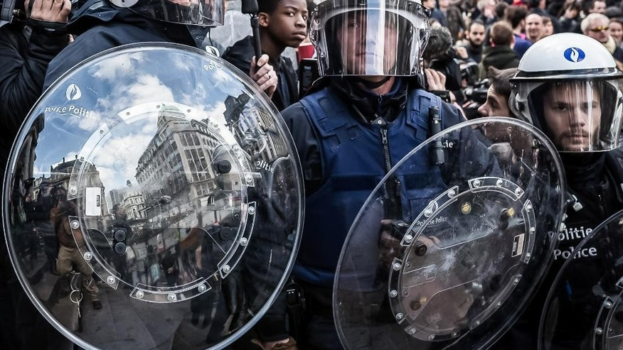 Riot police attend a memorial site during a protest by right wing demonstrators at the Place de la Bourse in Brussels, Sunday, March 27, 2016. In a sign of the tensions in the Belgian capital and the way security services are stretched across the country, Belgium's interior minister appealed to residents not to march Sunday in Brussels in solidarity with the victims. (AP Photo/Valentin Bianchi)