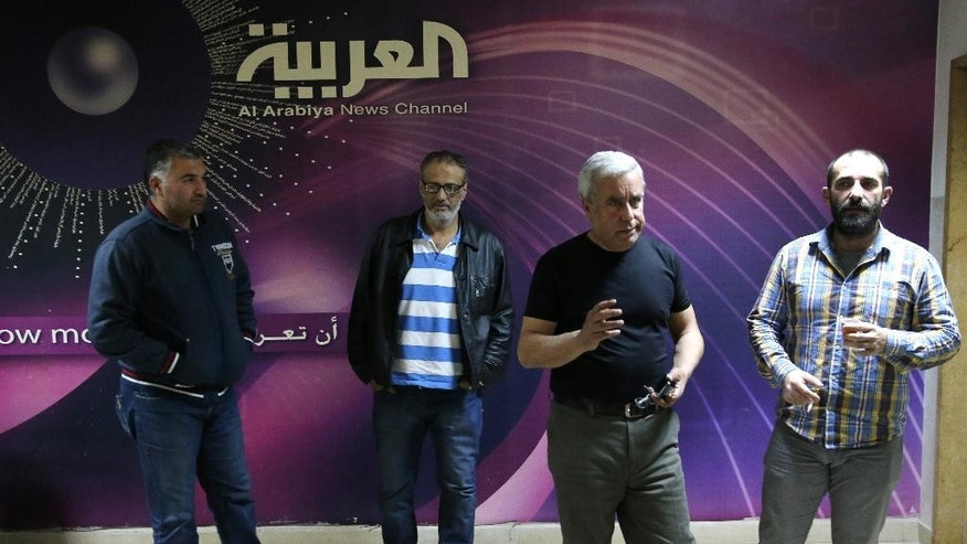 Lebanese cameramen and reporter who work at Al-Arabiya channel, stand at the entrance of their office, in Beirut, Lebanon, Friday, April 1, 2016.  Beirut-based employees of the Saudi-owned Al-Arabiya channel say the station has decided to shut down its Lebanon operation amid tensions between Riyadh and Beirut. Saudi Arabia has halted deals worth $4 billion for Lebanon and warned its citizens against travel to Lebanon in retaliation for the country's siding with Iran amid the Sunni kingdom's spat with the Shiite powerhouse. (AP Photo/Hussein Malla)