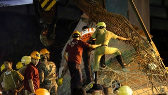 Indian soldiers and rescue workers work on a partially collapsed overpass in Kolkata, India, Thursday, March 31, 2016. A long section of a road overpass under construction collapsed Wednesday in a crowded Kolkata neighborhood, with tons of concrete and steel slamming into midday traffic, killing several and injuring many. (AP Photo/ Bikas Das)