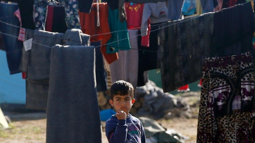 A boy stands by the hanging laundry in the makeshift refugee camp at the northern Greek border point of Idomeni, Greece, Thursday, March 31, 2016. More than 50,000 migrants remain stranded in Greece following border restrictions and closures by Austria and Balkan nations. (AP Photo/Darko Vojinovic)
