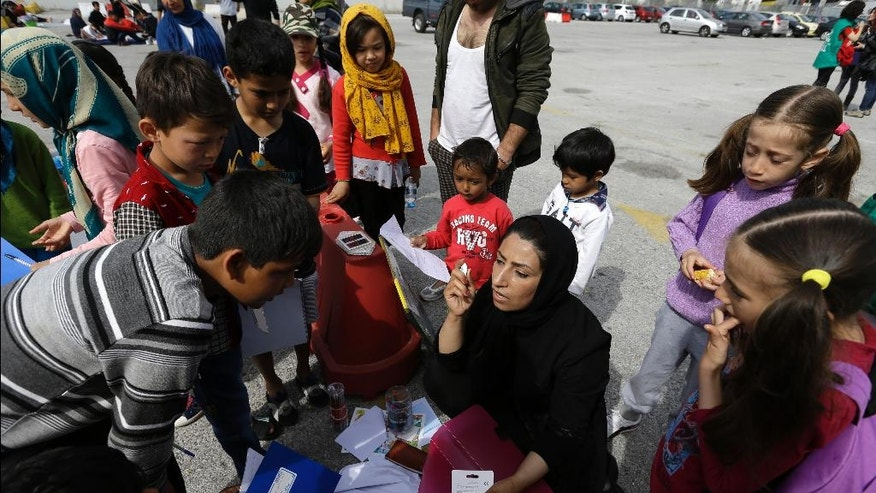 University teacher Ziaee Shole, center, speaks to Afghan children at the Athens port of Piraeus, on Friday, April 1, 2016. Shole, 32, migrant from the Iranian town of Shiraz started to educate the migrants' children the last two days. She has been staying with her Afghan husband and their two children for the last two weeks in a warehouse at the the port. About 5,300 stay at the biggest port of the country as more than 50,000 migrants remain stranded in Greece following border restrictions and closures by Austria and Balkan nations. (AP Photo/Thanassis Stavrakis)