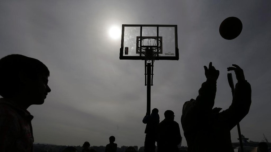 Boys play basketball at the Athens port of Piraeus, on Friday, April 1, 2016. About 5,300 stay at the biggest port of the country as more than 50,000 migrants remain stranded in Greece following border restrictions and closures by Austria and Balkan nations. (AP Photo/Thanassis Stavrakis)