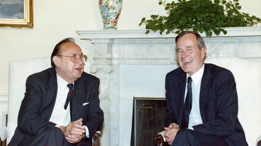 FILE - In this June 21, 1989 file photo West German Foreign Minister Hans-Dietrich Genscher, left, sits in the Oval Office in the White House in Washington, USA, sharing a laugh with U.S. President George Bush. Genscher died Friday, April 1, 2016 at the age of 89. (AP Photo/Barry Thumma, file)