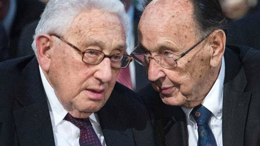 FILE - In this Oct. 9, 2014 file photo Former U.S. Secretary of State Henry Kissinger, left, talks to Hans-Dietrich Genscher, former foreign minister of West Germany, right, prior to a memorial service in the St Nikolai Church marking the 25th anniversary of the peaceful German revolution in Leipzig, Germany. Genscher died Friday, April 1, 2016 at the age of 89. (AP Photo/Jens Meyer, file)