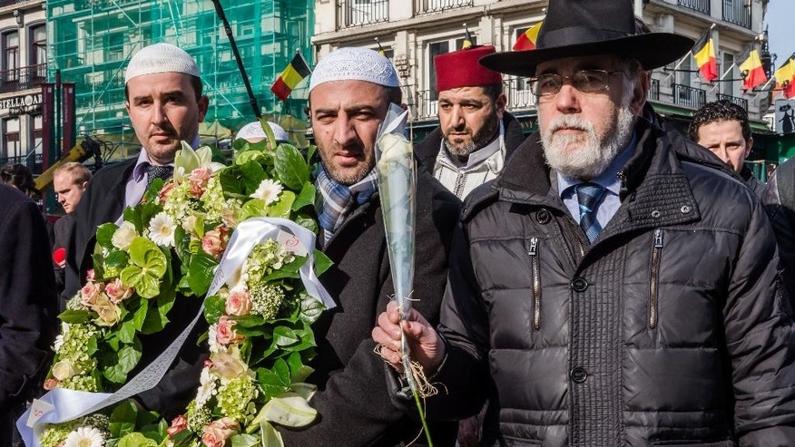 Brussels Grand Rabbi, Albert Guigui, right, together with other religious leaders attend a ceremony organized by the Belgian Muslim Executive at a memorial site for the victims of the Brussels attacks at the Place de la Bourse in Brussels, Belgium, Friday, April 1, 2016. (AP Photo/Geert Vanden Wijngaert)