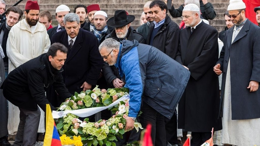 Chairman of the Belgian Muslim Executive Salah Echallaoui, 2nd left, Brussels Grand Rabbi, Albert Guigui, center, together with other religious leaders attend a ceremony organized by the Belgian Muslim Executive at a memorial site for the victims of the Brussels attacks at the Place de la Bourse in Brussels, Belgium, Friday, April 1, 2016. (AP Photo/Geert Vanden Wijngaert)