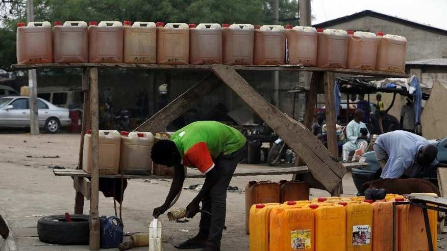 A man sells fuel on the road side in Kano, Nigeria, Friday, April 1, 2016. Nigeria's oil minister apologized this week for a fuel shortage that has created long lines at gas stations and left travelers stranded on highways in sub-Saharan Africa's top oil producing country. (AP Photo/Sunday Alamba)