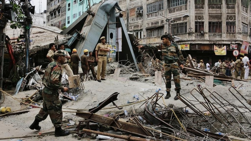 Security officers work on the area of a collapsed overpass in Kolkata, India, Friday, April 1, 2016. The overpass spanned nearly the width of the street and was designed to ease traffic through the densely crowded Bara Bazaar neighborhood in the capital of the east Indian state of West Bengal. About 100 meters (300 feet) of the overpass fell, while other sections remained standing. (AP Photo/Bikas Das)