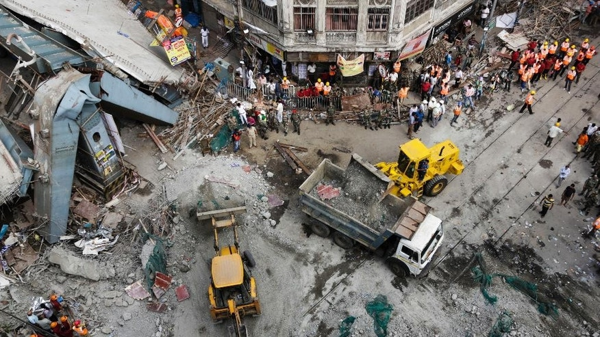 Excavator machines remove debris of a partially collapsed overpass in Kolkata, India, Friday, April 1, 2016. The overpass spanned nearly the width of the street and was designed to ease traffic through the densely crowded Bara Bazaar neighborhood in the capital of the east Indian state of West Bengal. About 100 meters (300 feet) of the overpass fell, while other sections remained standing. (AP Photo/Bikas Das)