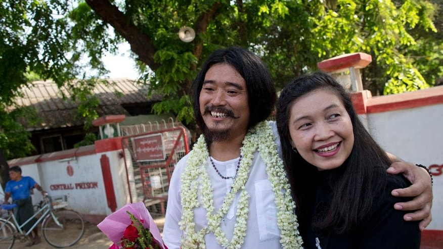 Ethnic Kachin activist Patrick Kum Ja Lee, left, smiles after posing for a picture with his wife and prominent Human Rights activist May Sabe Phyu, right, outside insein prison in Yangon, Myanmar, Friday, April 1, 2016. Patrick Kum Ja Lee, accused of sharing a post poking fun at Myanmar's army chief on Facebook, was released on Friday after he spent six month's imprisonment. (AP Photo/ Gemunu Amarasinghe)