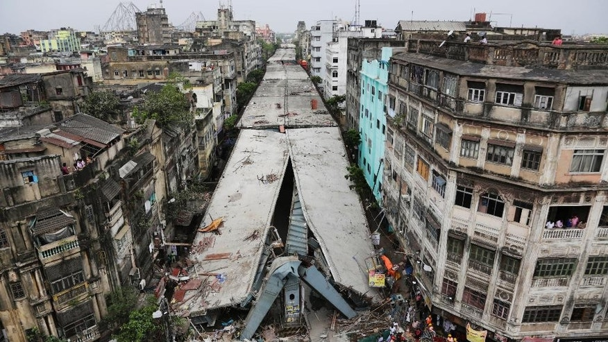 General view shows a partially collapsed overpass in Kolkata, India, Friday, April 1, 2016. The overpass spanned nearly the width of the street and was designed to ease traffic through the densely crowded Bara Bazaar neighborhood in the capital of the east Indian state of West Bengal. About 100 meters (300 feet) of the overpass fell, while other sections remained standing. (AP Photo/Bikas Das)