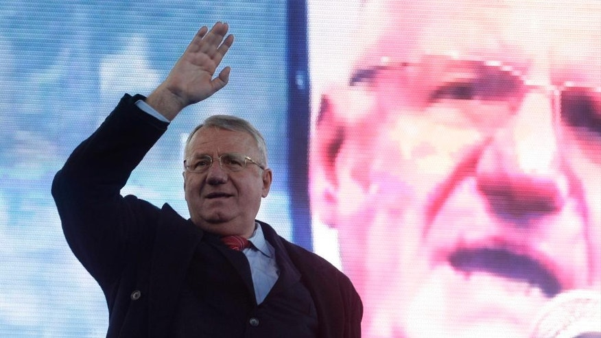 In this Thursday, March 24, 2016 file photo, Serbian ultranationalist and war crimes suspect Vojislav Seselj waves to supporters during a rally in Belgrade, Serbia. The judgment in Seselj's case at the U.N. war crimes court is scheduled for Thursday, March 31. (AP Photo/Andrej Cukic, File)