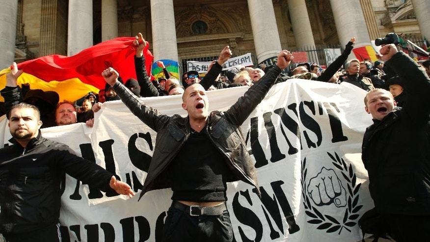 "FILE - In this Sunday, March, 27, 2016 file photo, right-wing demonstrators chant slogans next to one of the memorials to the victims of the recent Brussels attacks, at the Place de la Bourse in Brussels. As extreme-right groups threaten to take Molenbeek neighborhood by storm Saturday, April 2, community leaders fear its predominantly Muslim young people will fight back. ""They don't trust the police and they aren't going to take it,"" said Fouad Ben Abdelkader, a teacher in the neighborhood. On Thursday he joined a meeting of a couple dozen community leaders and mentors to neighborhood youths who feel adrift in mainstream Belgian society. The group of community organizers was looking for ways to head off an escalation of violence in the largely Muslim neighborhood, hoping to avoid a situation like occurred last Sunday when hundreds of black-clad hooligans shouting Nazi slogans disrupted a memorial at Brussels' Bourse square for the 32 victims of the March 22 attacks on the airport and subway system. (AP Photo/Alastair Grant, file)"
