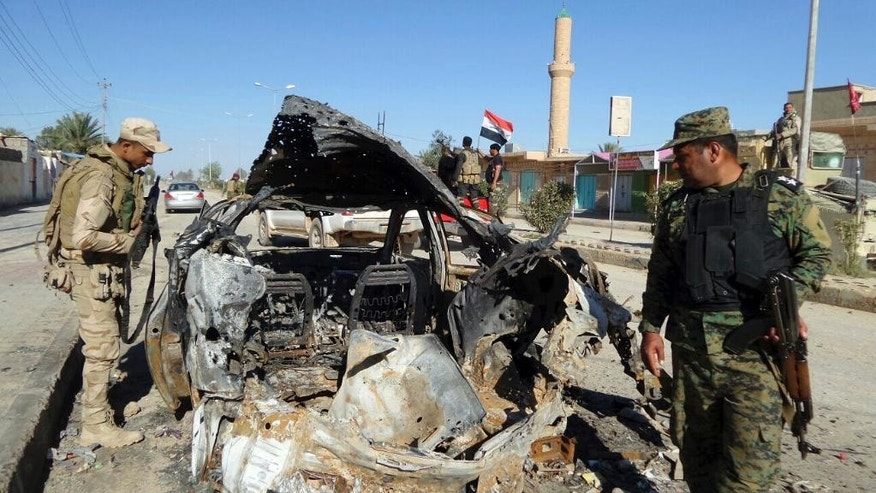 In this Wednesday, March 30, 2016 photo, Iraqi security forces inspect a destroyed vehicle used by Islamic State fighters, after regaining control of the town of Kubaisa, Anbar province, west of Baghdad, Iraq.  Since IS swept across much of northern and western Iraq in the summer of 2014, Iraqi authorities have waged a full-scale war to win back territory from the extremist group. (AP Photo)