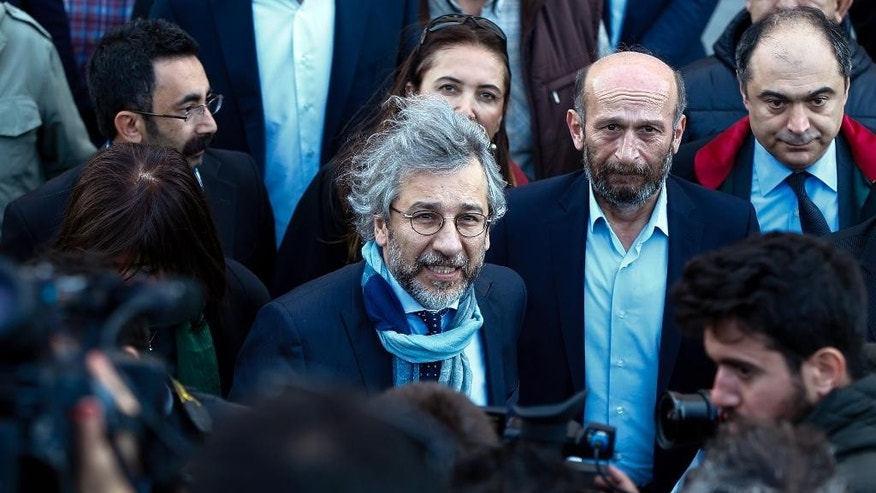 Can Dundar, the editor-in-chief of opposition newspaper Cumhuriyet, center-left, and Erdem Gul, the paper's Ankara representative, center-right, speak to the media before the start of their trial in Istanbul, Friday, April 1, 2016. The trial of two Turkish journalists accused of revealing state secrets and helping a terror organization over their reports on alleged government-arms smuggling to Syrian rebels was resumed on Friday after opposition lawmakers in the first hearing refused to leave the courthouse in defiance of a ruling that the case should be behind closed doors. (AP Photo/Emrah Gurel)