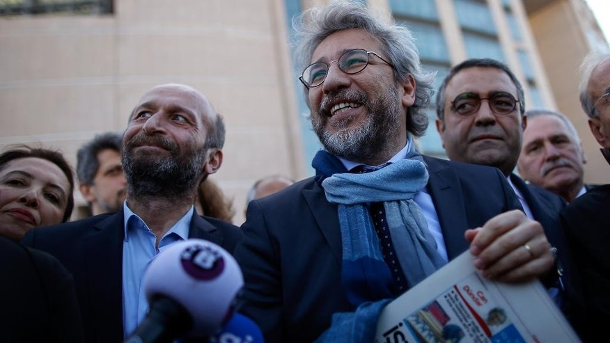 Can Dundar, the editor-in-chief of opposition newspaper Cumhuriyet, right, and Erdem Gul, the paper's Ankara representative, left, speak to the media before the start of their trial in Istanbul, Friday, April 1, 2016. The trial of two Turkish journalists accused of revealing state secrets and helping a terror organization over their reports on alleged government-arms smuggling to Syrian rebels was resumed on Friday after opposition lawmakers in the first hearing refused to leave the courthouse in defiance of a ruling that the case should be behind closed doors. .(AP Photo/Emrah Gurel)