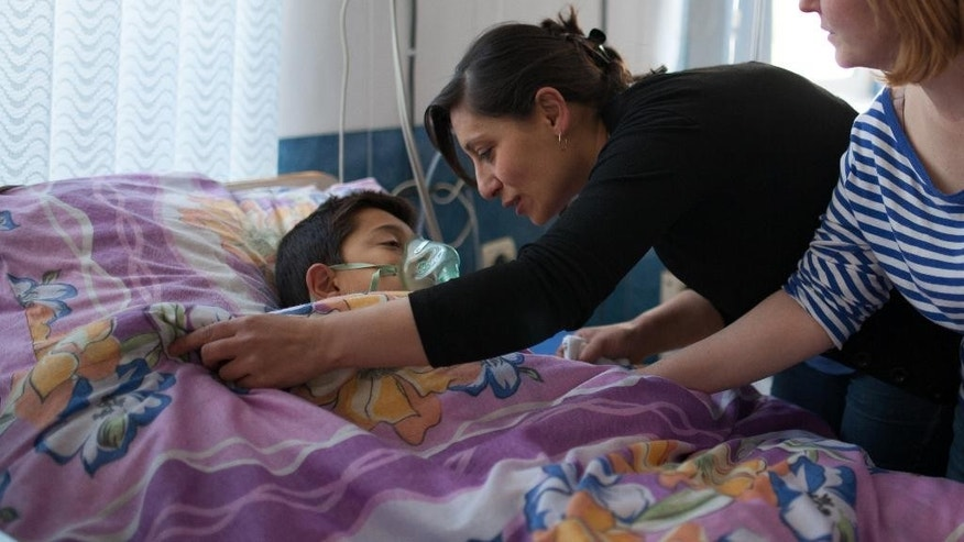 12-year-old Gevorg Grigoryan's mother pulls a blanket up for her son who was wounded in a missile barrage by Azerbaijani forces, in a hospital in Stepanakert, in the separatist Nagorno-Karabakh region, Armenia, Saturday, April 2, 2016. Heavy fighting has broken out between Armenian and Azerbaijani forces along the front lines of the separatist Nagorno-Karabakh region, reportedly killing at least one child in what one official called the worst clashes since 1994. (Areg Balayan/PAN Photo via AP)