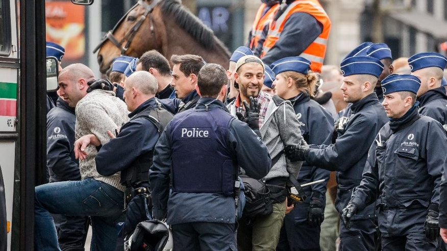 Policemen detain people at the Place de la Bourse in Brussels, Belgium, Saturday, April 2, 2016. Authorities had banned all marches in Brussels, after a far-right group announced its plans to hold an anti-Muslim rally in the city. (AP Photo/Olivier Matthys)