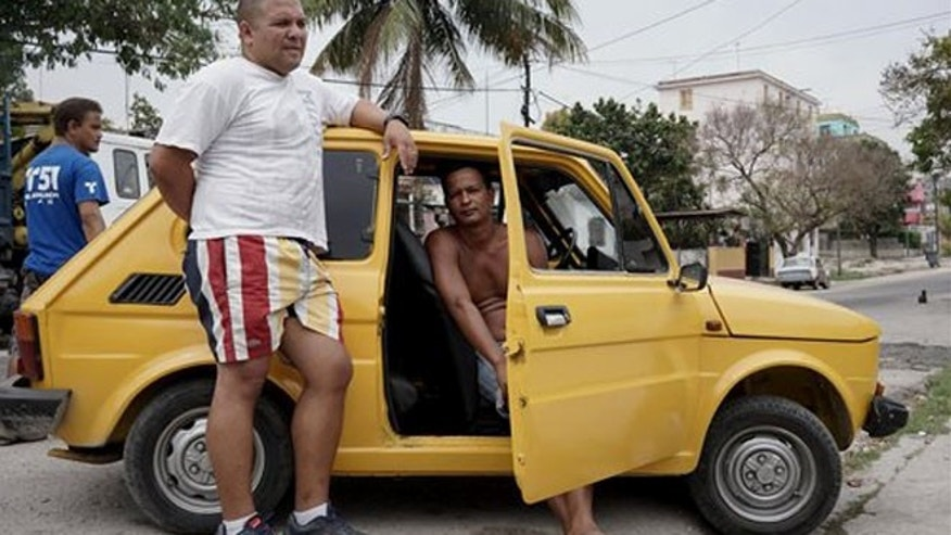 In this March 29, 2016 photo, Boris Lazo, left, and Yandy Aquila, wait outside an automobile body shop in Havana, Cuba. Both were doubtful Obamas visit and the U.S.-Cuba normalization would do much to improve their daily lives. Neither has family in the U.S. or any other form of economic support. Business benefits those who have businesses, Aquila said. But us? (AP Photo/Christine Armario)