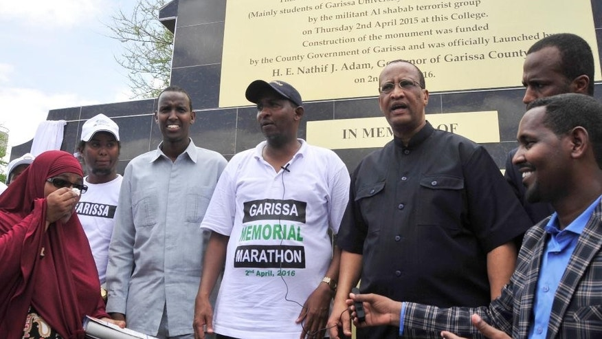 Adam Duale, center, leader of the majority in Kenyan Parliament, and Garissa County Governor Nathif Adam, second right, pose in front of the memorial plaque at Garissa University, Garissa, Kenya, Saturday, April 2, 2016.  Kenya has marked the first anniversary of the Garissa University attack in which more than 148 people, most of them students, died at the hands of extremist gunmen. Hundreds gathered at the Garissa University in eastern Kenya on Saturday to remember the incident, one of the country's worst-ever terrorist attacks.(AP Photo/Kevin Midigo)