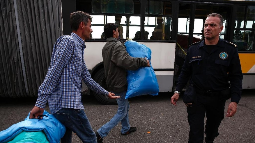 Men carry their belongings to a bus as they and other refugees and migrants are transferred to an organized camp, at the port of Piraeus, near Athens, on Saturday, April 2, 2016. Greece is pressing ahead with plans to start deporting migrants and refugees back to Turkey next week, despite mounting concern from the United Nations and human rights organizations that Syrians could be denied proper protection while some are allegedly even being forced back into their war-torn country. (AP Photo/Yorgos Karahalis)