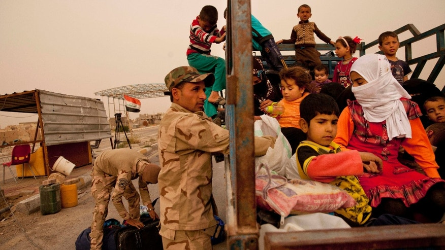 In this Sunday, March 20, 2016 photo, Iraq soldiers search a convoy of families fleeing Islamic State-held Hit, Iraq, at a checkpoint on the western edge of Ramadi, Iraq.