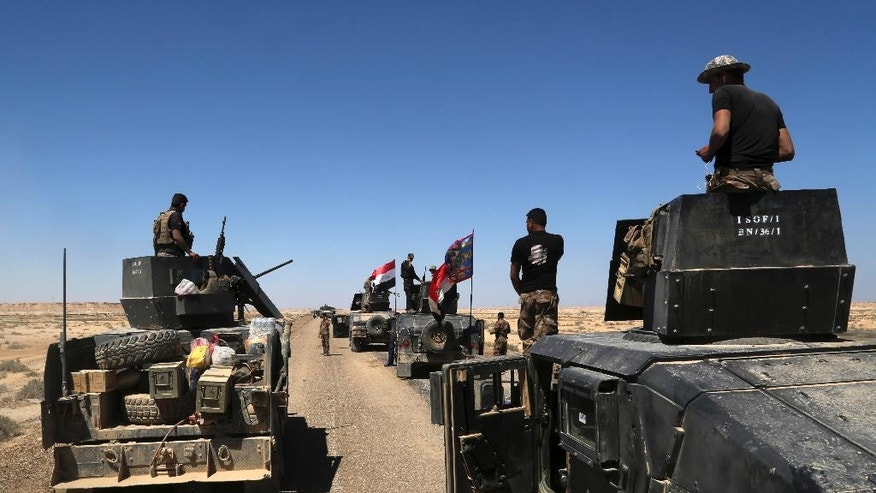 Iraqi security forces prepare to attack Islamic State group positions in Hit, 85 miles (140 kilometers) west of Baghdad, Iraq, Saturday, April 2, 2016. The United Nations mission to Iraq said in a statement Friday that violence killed at least 1,119 Iraqis in March, a sharp increase from the previous month, as the Islamic State group stepped up attacks on civilians despite suffering battlefield setbacks. (AP Photo/Khalid Mohammed)
