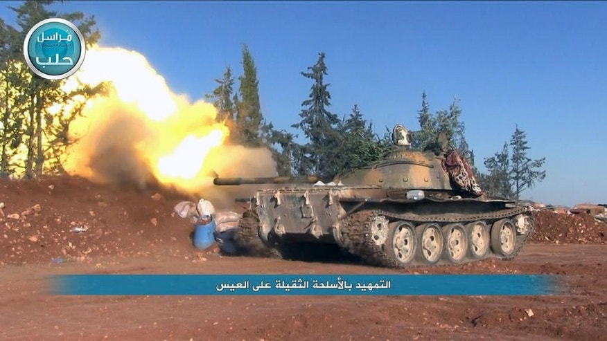 "This image posted on the Twitter page of Syria's al-Qaida-linked Nusra Front on Friday, April 1, 2016, shows a Nusra Front tank firing at Syrian troops and pro-government gunmen in the northern village of al-Ais in Aleppo province, Syria. The Britain-based Syrian Observatory for Human Rights says 12 Hezbollah fighters were killed and dozens were wounded in Saturday's attack by militants led by al-Qaida's Syria branch — known as the Nusra Front — on the northern village of al-Ais. The title in Arabic that reads ""introduction attacks with heavy weapons on al-Ais."" (Al-Nusra Front via AP)"