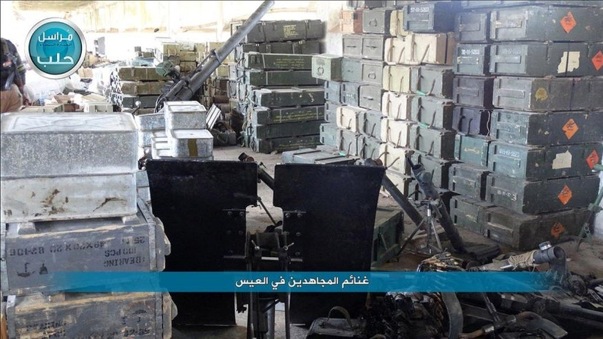 "This image posted on the Twitter page of Syria's al-Qaida-linked Nusra Front on Saturday, April 2, 2016, shows boxes of ammunition and weapons captured by Nusra Front during the militants attack on the northern village of al-Ais in Aleppo province, Syria. The Britain-based Syrian Observatory for Human Rights says 12 Hezbollah fighters were killed and dozens were wounded in Saturday's attack by militants led by al-Qaida's Syria branch — known as the Nusra Front — on the northern village of al-Ais. The title in Arabic that reads ""spoils by the holy warriors in al-Ais."" (Al-Nusra Front via AP)"