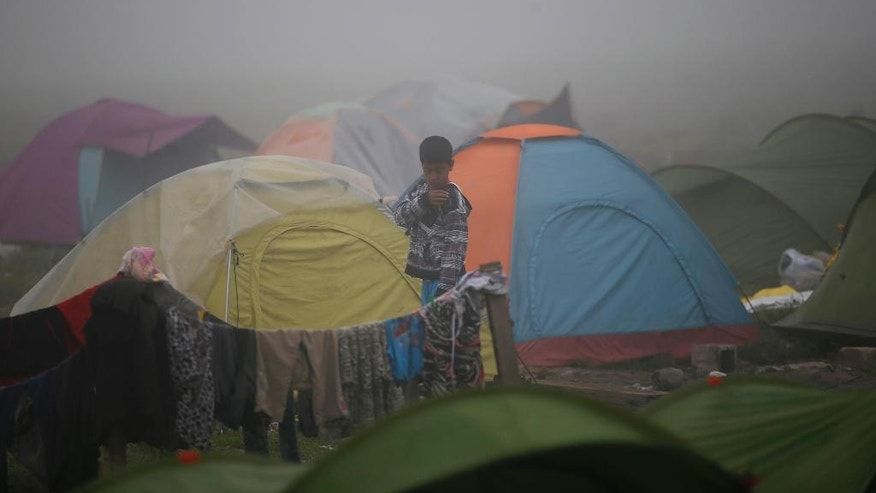 A boy walks through the makeshift refugee camp at the northern Greek border point of Idomeni, Greece, Saturday, April 2, 2016. Greece is pressing ahead with plans to start deporting migrants and refugees back to Turkey next week, despite mounting concern from the United Nations and human rights organizations that Syrians could be denied proper protection while some are allegedly even being forced back into their war-torn country. (AP Photo/Darko Vojinovic)