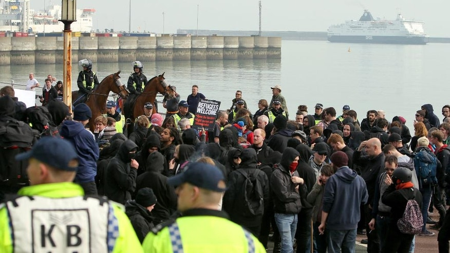 Police officers monitor as members of an Anti-Racism Network mount a counter demonstration, near the ferry docks in Dover, England, Saturday April 2, 2016. The group are protesting against far-right groups who are marching nearby, protesting against the arrival of immigrants. (Steve Parsons / PA via AP) UNITED KINGDOM OUT - NO SALES - NO ARCHIVES