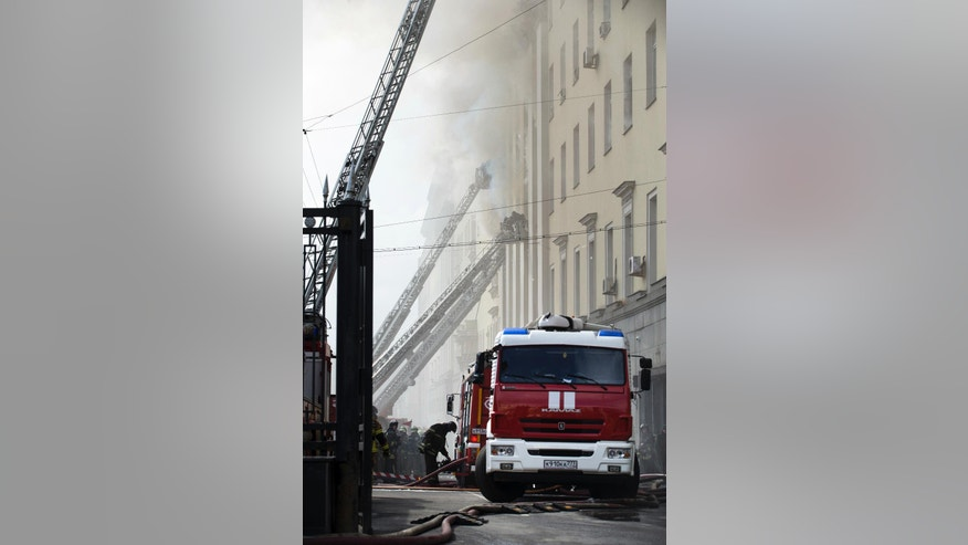 Firefighters work to put out a blaze at a building of Russian Defense Ministry in Moscow, Russia, Sunday, April 3, 2016. A building of the Russian Defense ministry is on fire in central Moscow, the city's law enforcement bodies told Russian news agency TASS on Sunday. (AP Photo/Ivan Sekretarev)