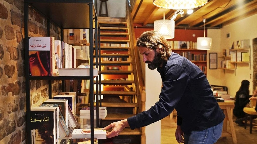 In this photo taken on Friday, April 1, 2016, Syrian refugee Samer Al-Kadri, founder and owner of Pages, a rustic three story-Arabic language bookshop, removes a book at his store in Istanbul, Turkey. The bookstore has become an anchor for many Syrians who have stayed put in Turkey but crave a taste of home. Al-Kadri, a refugee himself, says the store strives to be a bridge between Syrians, Turks and the myriad of foreigners who visit the city. Its weekly program includes oriental music concerts and, starting soon, language exchanges in Arabic, English and Turkish. Books are available in all three languages. (AP Photo/Bram Janssen)