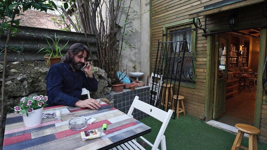 In this photo taken on Friday, April 1, 2016, Syrian refugee Samer Al-Kadri, founder and owner of Pages, a rustic three story-Arabic language bookshop, sits outside his store in Istanbul, Turkey. The bookstore has become an anchor for many Syrians who have stayed put in Turkey but crave a taste of home. Al-Kadri, a refugee himself, says the store strives to be a bridge between Syrians, Turks and the myriad of foreigners who visit the city. Its weekly program includes oriental music concerts and, starting soon, language exchanges in Arabic, English and Turkish. Books are available in all three languages. (AP Photo/Bram Janssen)