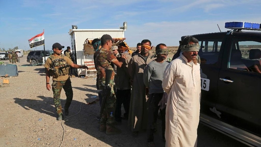 Iraqi security forces detain suspected members of the Islamic State group for interrogation after the men were found among civilians returning to Ramadi for the first time since the city was taken back by Iraqi government forces earlier this year, at a checkpoint in Ramadi, Iraq, Sunday, April 3, 2016. (AP Photo/Khalid Mohammed)