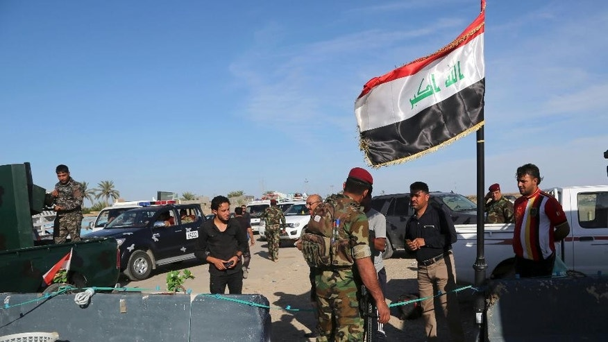 Iraqi security forces check identification documents at a checkpoint near the entrance to Ramadi, 70 miles (115 kilometers) west of Baghdad, Iraq, Sunday, April 3, 2016. Thousands of civilians have returned to the city after Iraqi government forces retook the Anbar provincial capital from the Islamic State group earlier this year. (AP Photo/Khalid Mohammed)