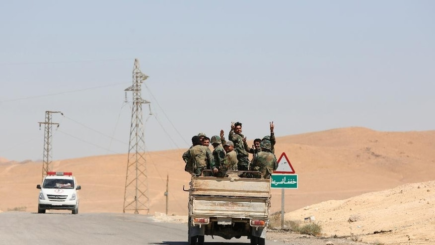 Syrian soldiers flash the v-victory sign in the ancient city of Palmyra on Friday, April 2, 2016. An Associated Press crew visiting the town Friday witnessed firsthand the destruction inflicted by the extremist group on the town's famed archaeological site, less than a mile away from the modern-day town of the same name, now completely deserted. (AP Photo)