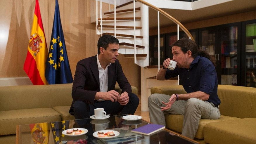 Spain's Socialist Party leader Pedro Sanchez, left, talks to Podemos Party leader Pablo Iglesias before their meeting at the Spanish parliament in Madrid, Wednesday, March 30, 2016. (AP Photo/Francisco Seco)