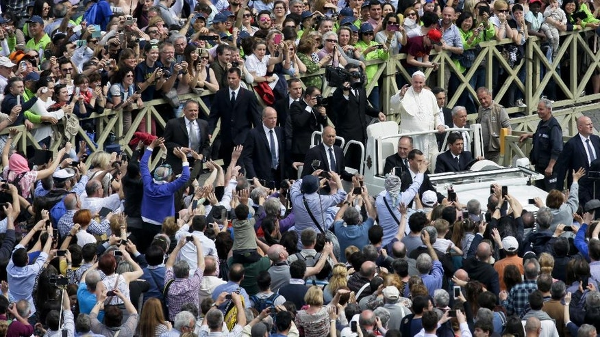 Faithful and tourists photograph Pope Francis as he makes a tour of St. Peter's Square at the end of a Mass for the the Holy Year of Mercy, at the Vatican, Sunday, April 3, 2016. (AP Photo/Alessandra Tarantino)
