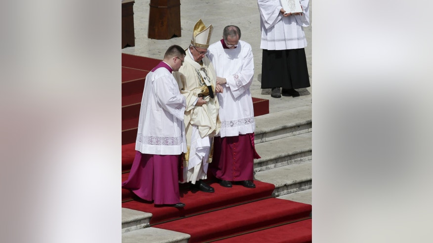 Pope Francis is assisted as he walks down the steps after celebrating a Mass for the Holy Year of Mercy, in St. Peter's Square at the Vatican, Sunday, April 3, 2016. (AP Photo/Alessandra Tarantino)