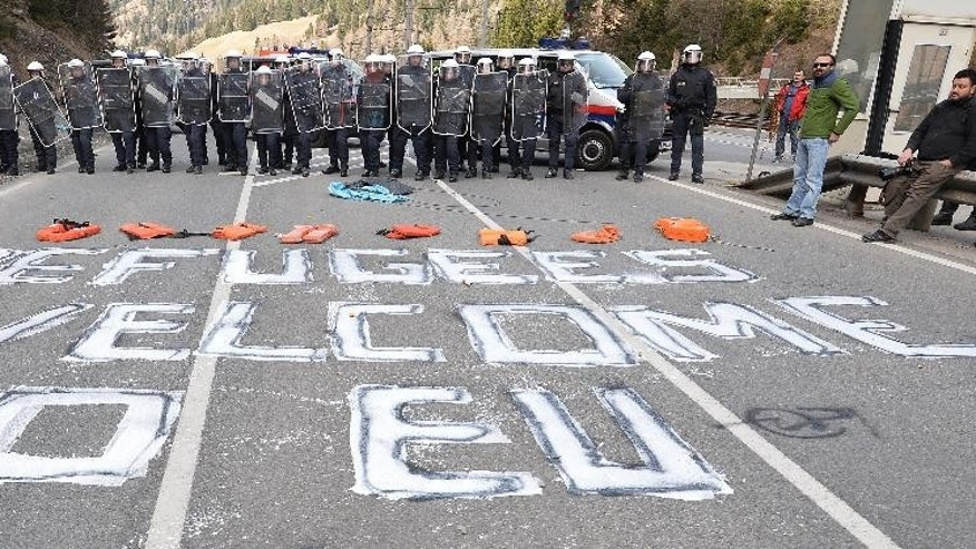"""Refugees wellcome to EU"" is painted on a street in front of Austrian police officers in thevillage of Brenner on the Italian-Austrian border, Sunday, April 3, 2016.   Austria's defense minister said his country will deploy soldiers at a key Alpine pass to stop migrants arriving from Italy. Hans Peter Doskozil told German daily Die Welt that the move anticipates a shift in migrant flows from the Turkey-Greece route to the central Mediterranean. In an interview published Saturday, the newspaper quotes Doskozil saying that the military can provide ""considerable support to border security"" at the Brenner pass.(AP Photo/Kerstin Joensson)"