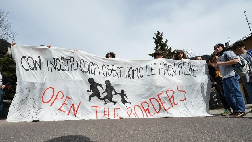 A protester  hold a banner in the  Italian village of Brenner on the Italian-Austrian border, Sunday, April 3, 2016. (AP Photo/Kerstin Joensson)