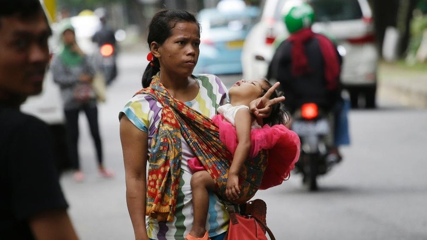 "In this Friday, April 1, 2016, photo, a woman carries her baby as she signals to show that she's for hire as a ""jockey"" to help drivers cheat a peak time traffic rule of three people to one car during rush hour, at the main business district in Jakarta, Indonesia. Traffic clogged Jakarta planned to suspend the peak time traffic rule this week raising concerns among the jockeys that they could lose their way to eke out living. (AP Photo/Achmad Ibrahim)"